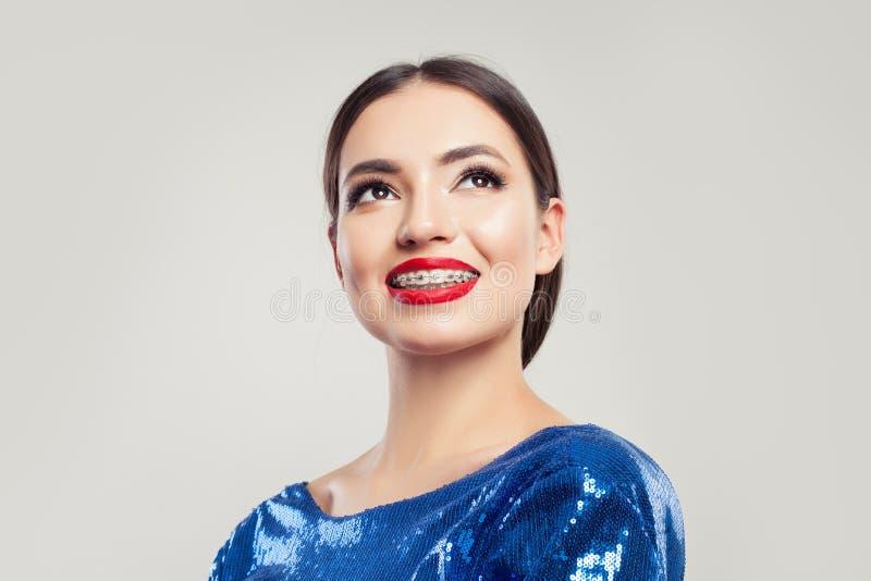 Vrolijk meisje in steunen die en omhoog op witte achtergrond glimlachen kijken royalty-vrije stock fotografie