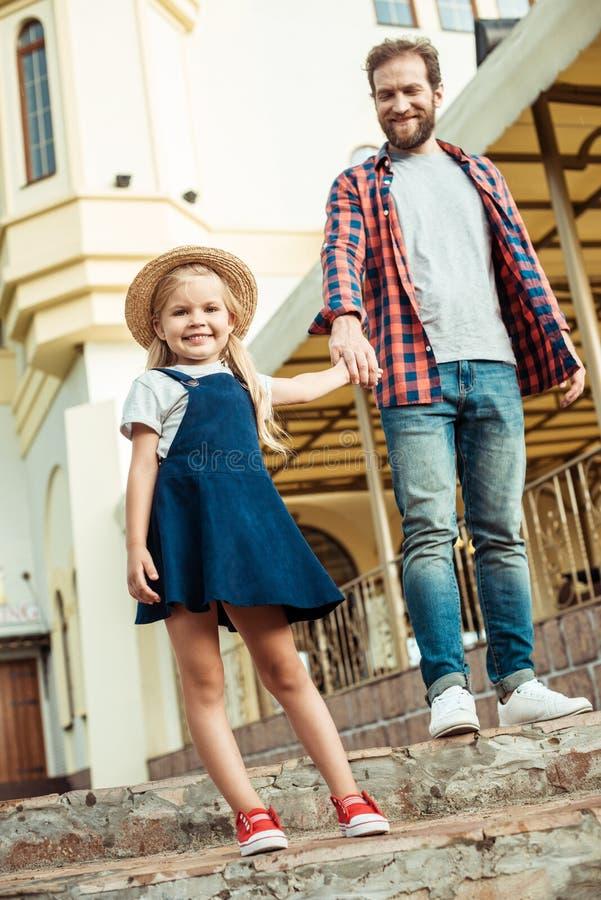 vrolijk meisje in strohoed en vaderholdingshanden samen terwijl status stock fotografie