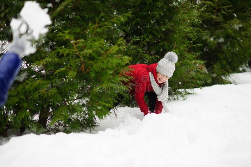 Vrolijk meisje van schoolleeftijd in een rode jasjespelen met iemand in sneeuwballen royalty-vrije stock foto
