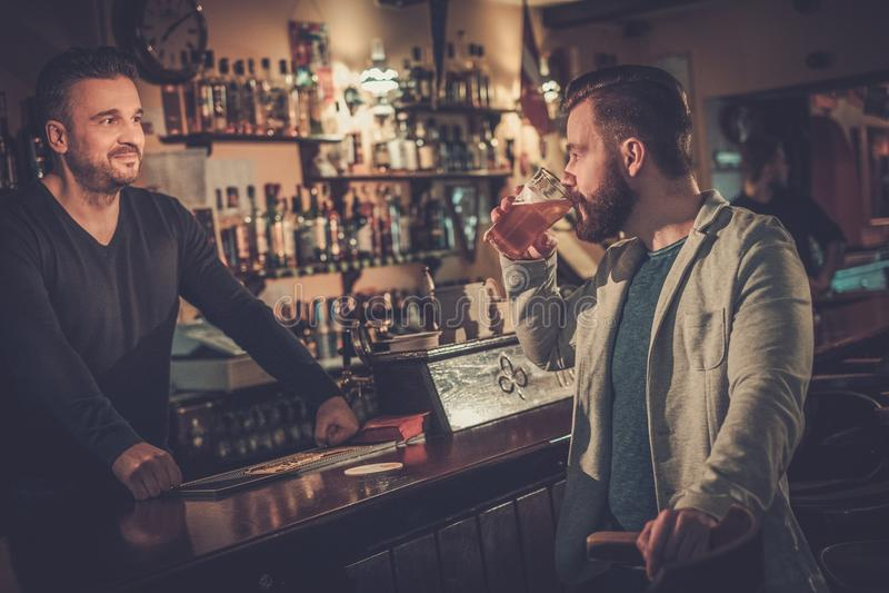 Vrolijk mens het drinken ontwerpbier bij barteller in bar stock foto's