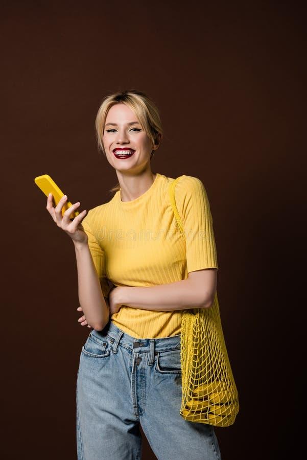 vrolijk modieus blondemeisje met bananen in koordzak gebruikend gele smartphone en glimlachend bij camera royalty-vrije stock afbeeldingen