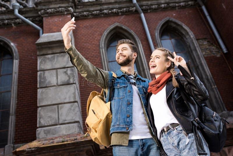 vrolijk modieus paar die selfie samen op smartphone nemen stock afbeelding