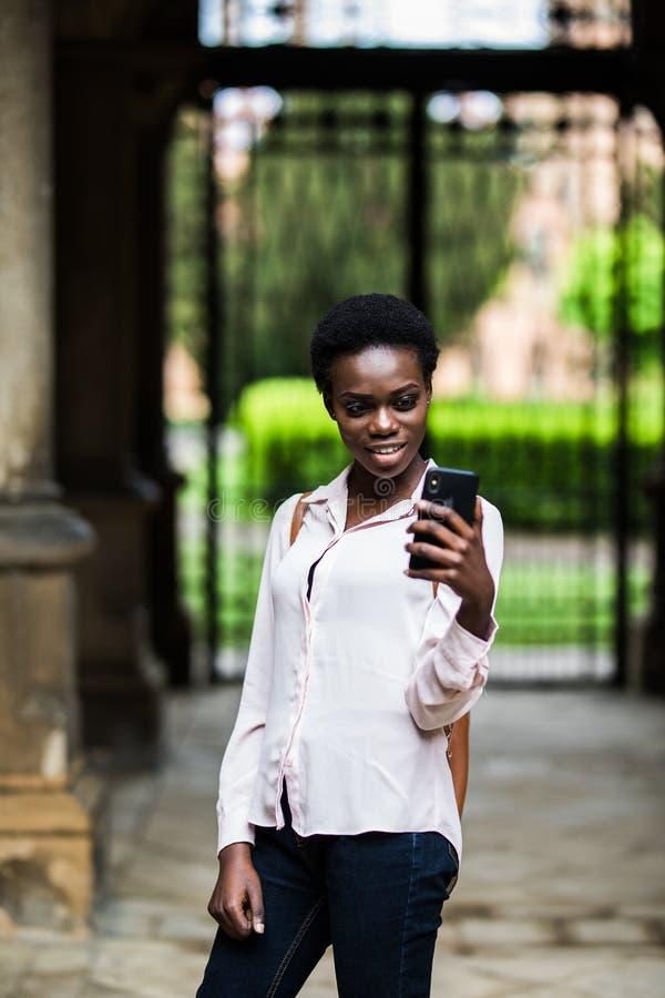 Vrolijk mooi afro Amerikaans wijfje die selfie op voorcamera van telefoon voor het publiceren in sociale netwerken in openlucht i stock afbeelding
