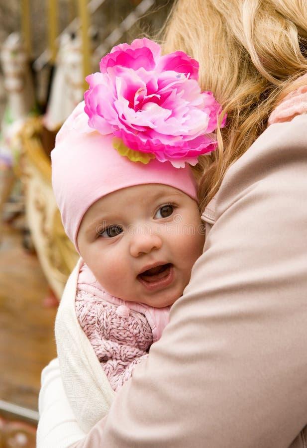 Vrolijk mooi babymeisje in de wapens van de moeder royalty-vrije stock afbeelding
