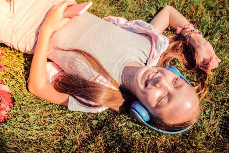 Vrolijk mooi meisje die blauwe oortelefoons dragen terwijl het luisteren muziek stock foto