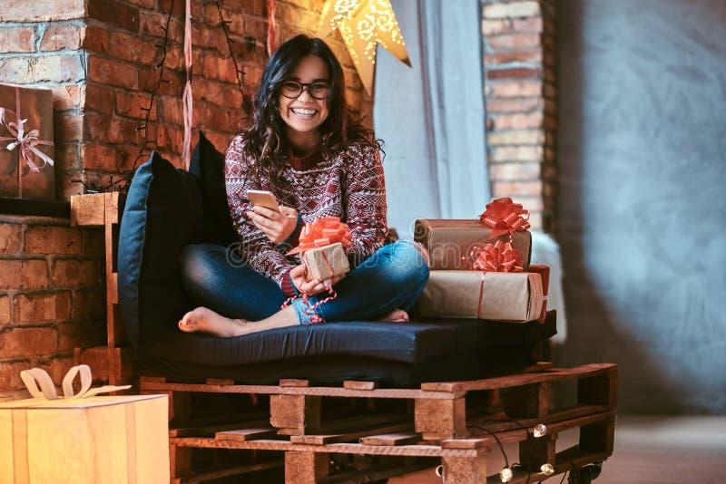 Vrolijk mooi meisje die een telefoon houden terwijl het zitten op een laag met giftdozen in een verfraaide ruimte met zolderbinne stock foto's
