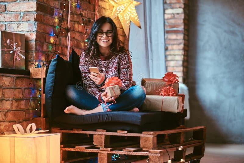 Vrolijk mooi meisje die een telefoon houden terwijl het zitten op een laag met giftdozen in een verfraaide ruimte met zolderbinne stock fotografie