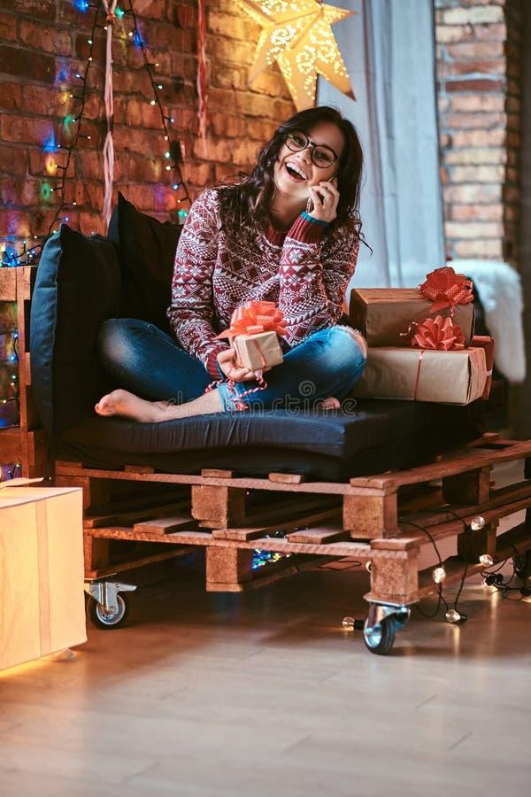 Vrolijk mooi meisje die telefonisch met vrienden spreken terwijl het zitten op een laag met giftdozen in een verfraaide ruimte me stock foto
