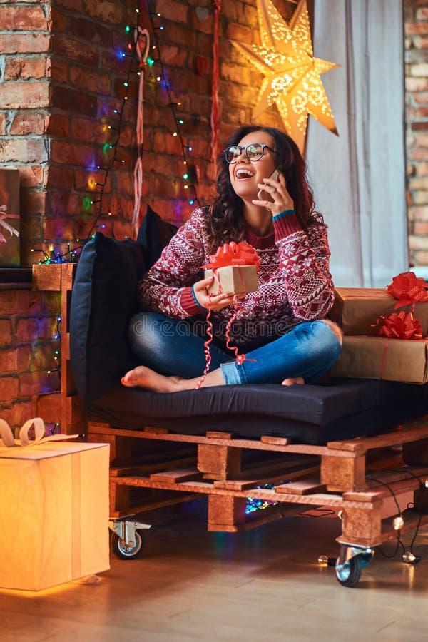 Vrolijk mooi meisje die telefonisch met vrienden spreken terwijl het zitten op een laag met giftdozen in een verfraaide ruimte me royalty-vrije stock foto