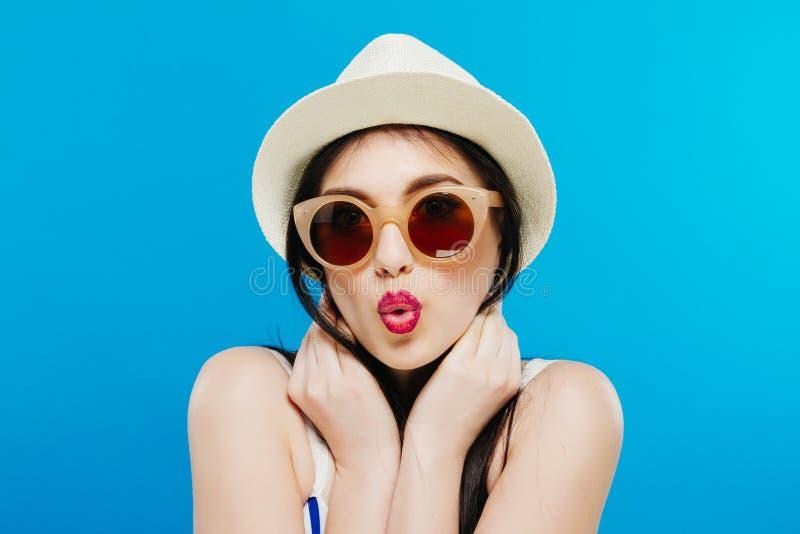 Vrolijk mooi meisje in hoed en zonglazen Wijd glimlachend, opzij kijkend en richtend De zomeruitrusting Taille omhoog stock afbeelding