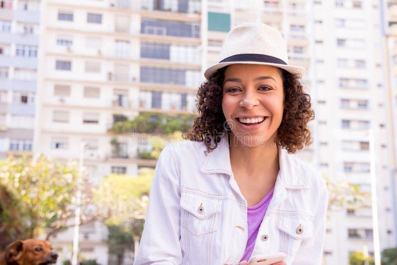 Vrolijk multiraciaal meisje die op stedelijke achtergrond met bouwstijl glimlachen stock afbeelding
