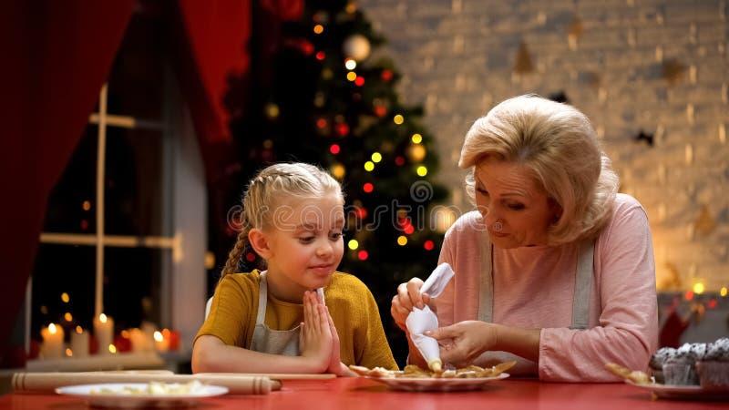 Vrolijk oma en meisje die koekjes voor Kerstmispartij verfraaien, gelukkige vakantie stock afbeelding