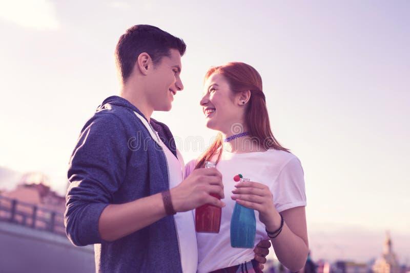 Vrolijk opgewekt jong paar die hun gevoel uitdrukken aan elkaar stock afbeelding