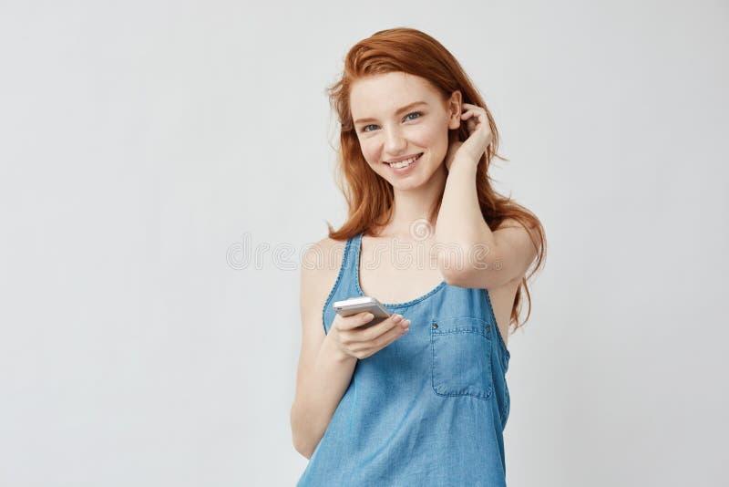 Vrolijk oprecht foxy meisje die met sproeten holdingstelefoon glimlachen royalty-vrije stock afbeeldingen