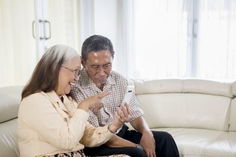 Vrolijk oud paar die een videogesprek thuis maken stock foto