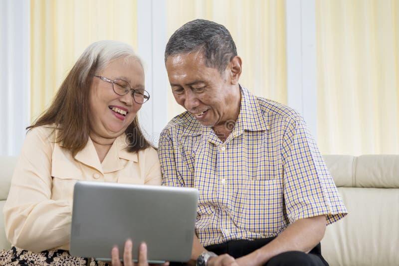 Vrolijk oud paar die laptop thuis met behulp van stock fotografie