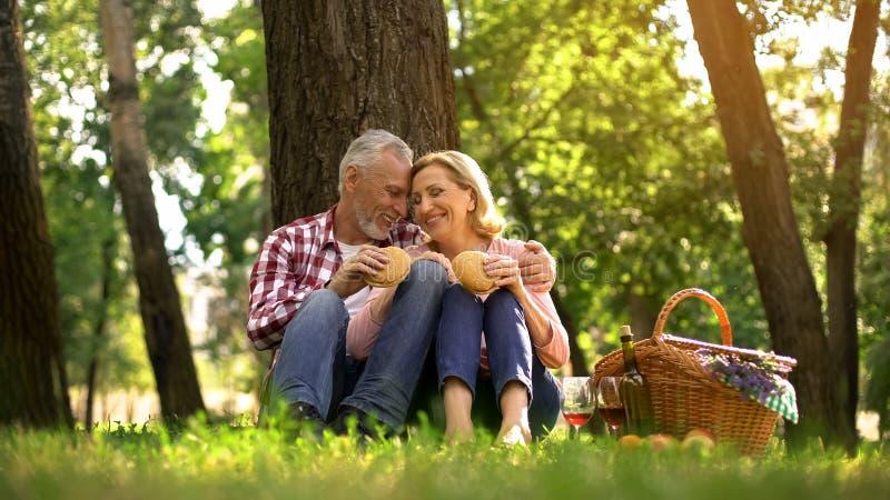 Vrolijk oud paar die op gras rusten en burgers, romantische datum in park eten stock foto's