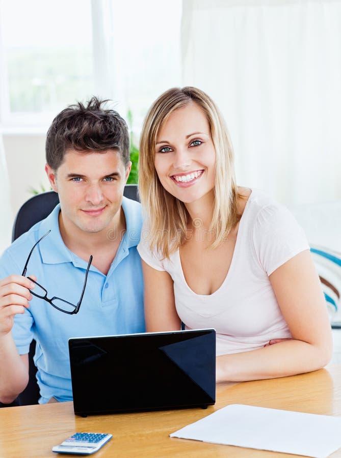 Vrolijk paar dat een laptop zitting samen gebruikt royalty-vrije stock foto's
