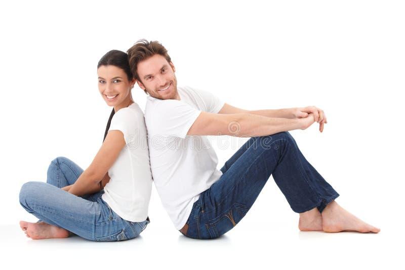 Vrolijk paar dat gelukkig op vloer glimlacht stock foto's