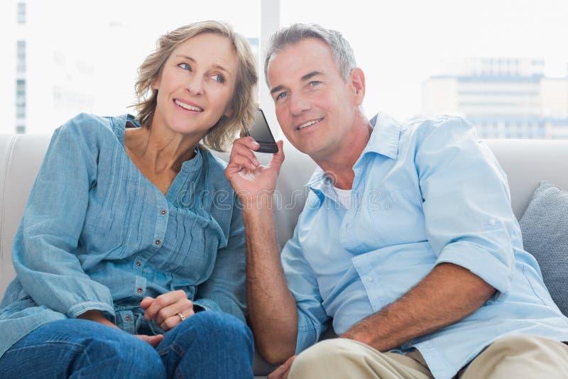 Vrolijk paar die aan mobiele telefoon samen luisteren stock foto's