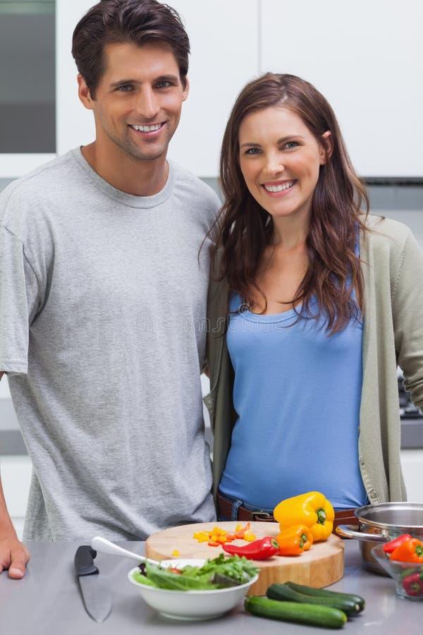 Vrolijk paar die bij camera glimlachen en groenten voorbereiden royalty-vrije stock foto