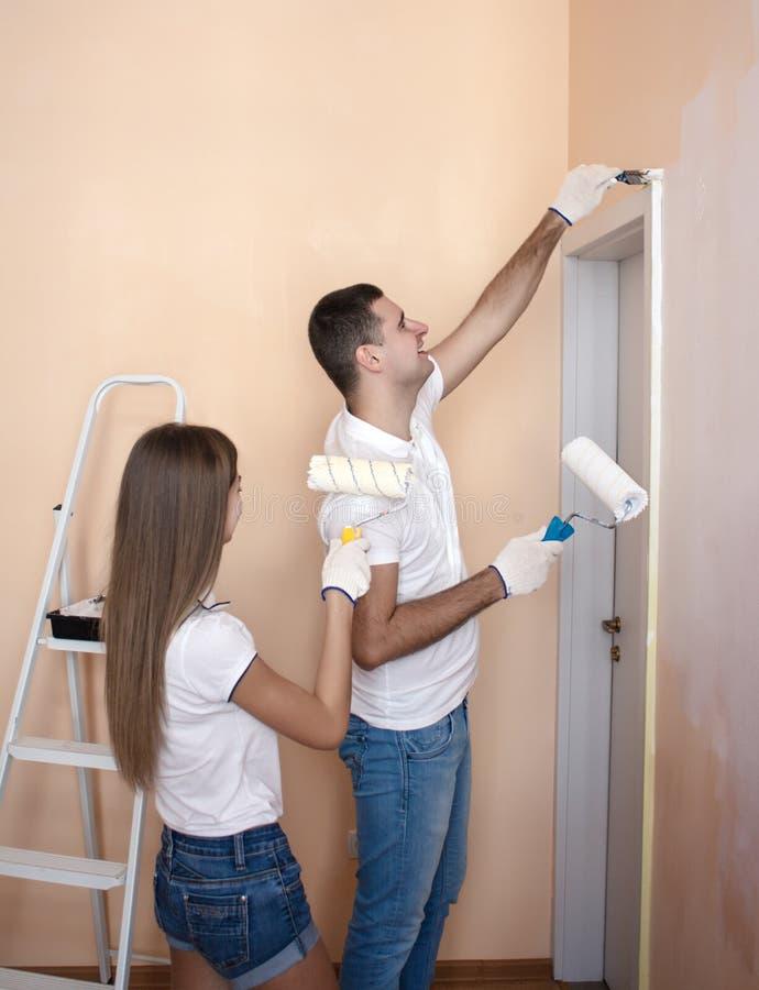 Vrolijk paar die binnenlandse muur van nieuw huis schilderen royalty-vrije stock afbeelding
