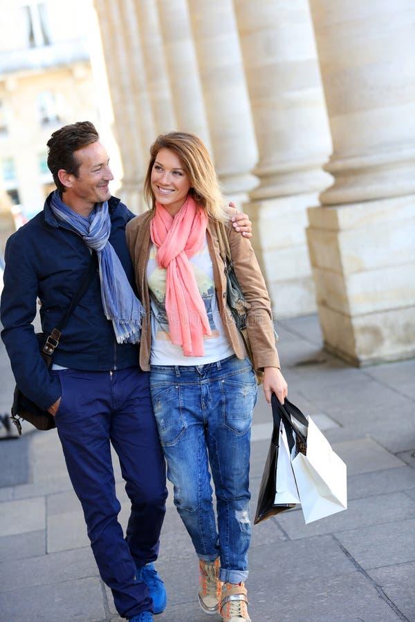 Vrolijk paar die een gang in stad het winkelen nemen royalty-vrije stock foto