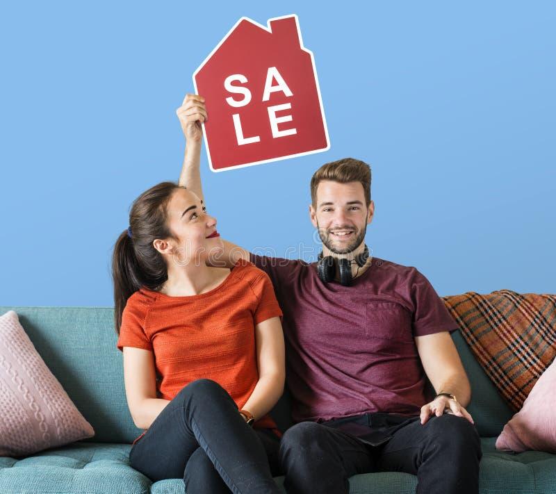Vrolijk paar die een pictogram van de huisverkoop houden stock fotografie