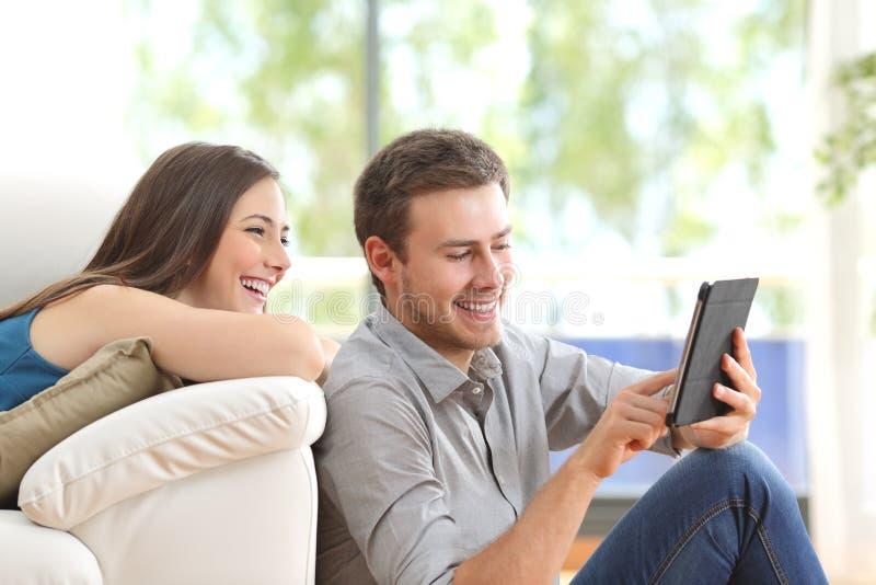 Vrolijk paar die een tablet thuis gebruiken royalty-vrije stock afbeeldingen