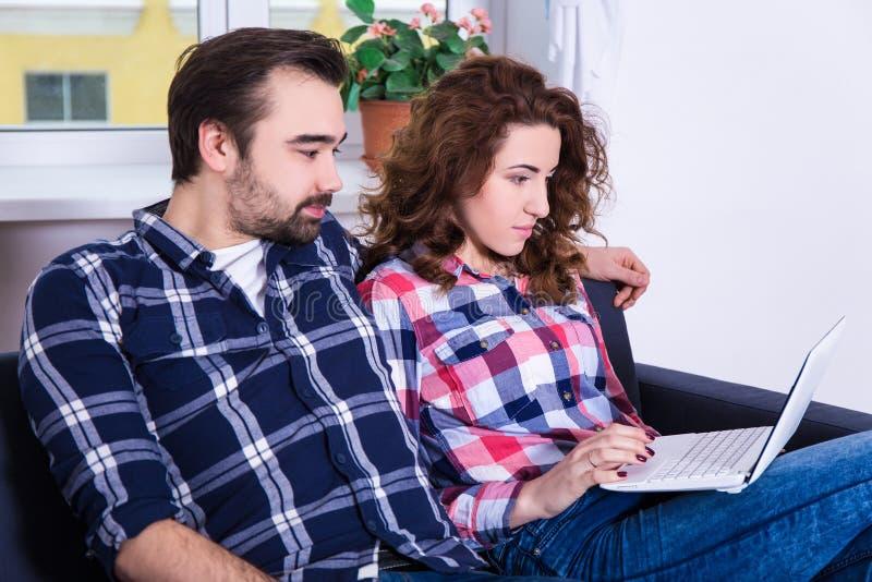 Vrolijk paar die iets op laptop thuis zoeken stock foto