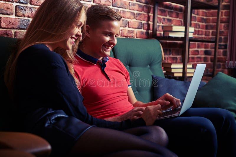 Vrolijk paar die iets zoeken die op laptop bij hom interesseren royalty-vrije stock foto