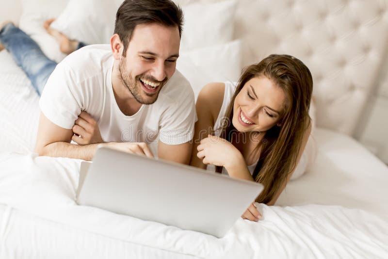 Vrolijk paar die laptop met behulp van die op hun bed thuis liggen stock afbeeldingen