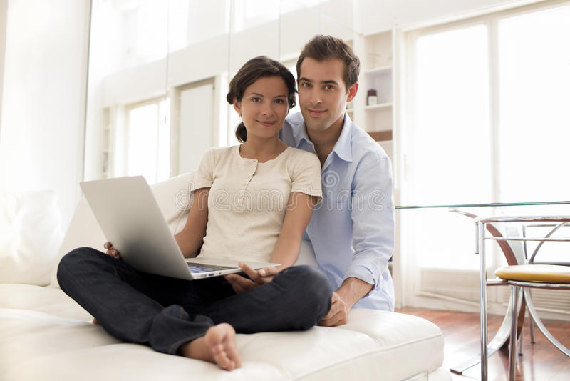 Vrolijk Paar die Laptop samen thuis met behulp van stock afbeeldingen