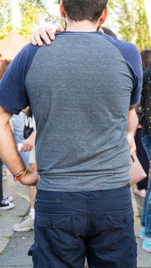 Vrolijk paar die in LGBT-festival koesteren Kerels die van elkaar in de straat met regenboogarmband houden stock fotografie