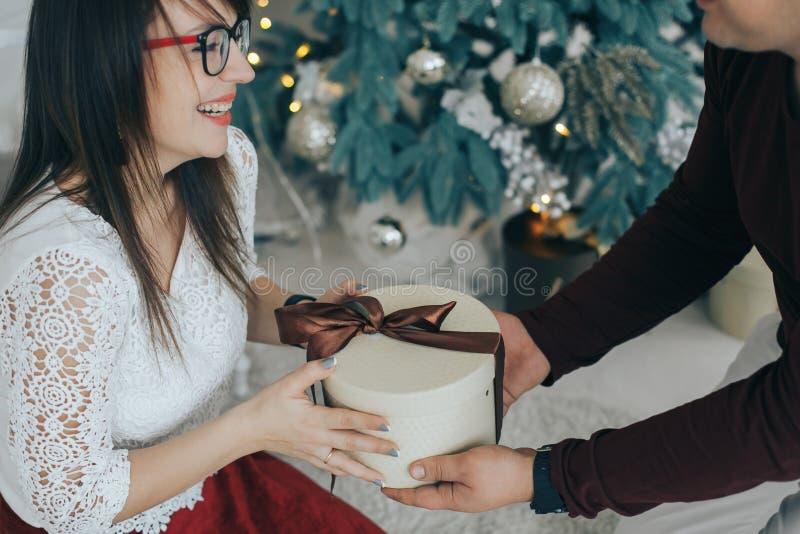Vrolijk paar die met gift in handen samen van op Kerstmisvooravond genieten royalty-vrije stock afbeeldingen