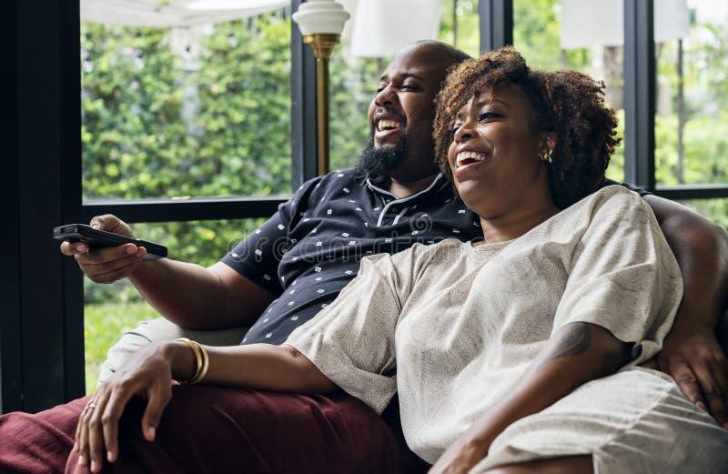 Vrolijk paar die op TV samen letten stock fotografie