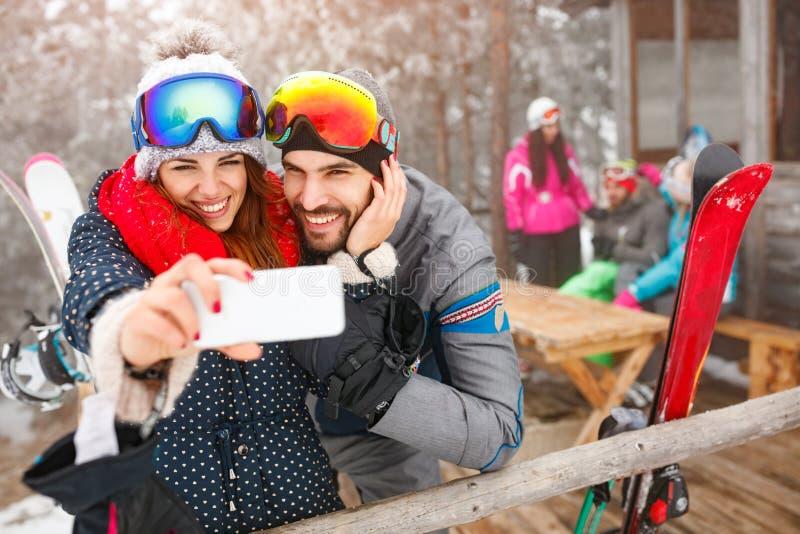 Vrolijk paar die selfie samen met celtelefoon nemen in sneeuw royalty-vrije stock foto's
