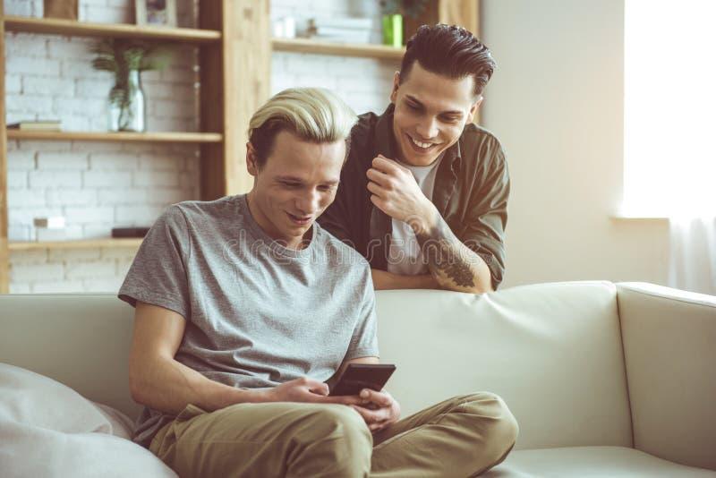 Vrolijk paar die telefoon het scherm en het glimlachen bekijken royalty-vrije stock fotografie