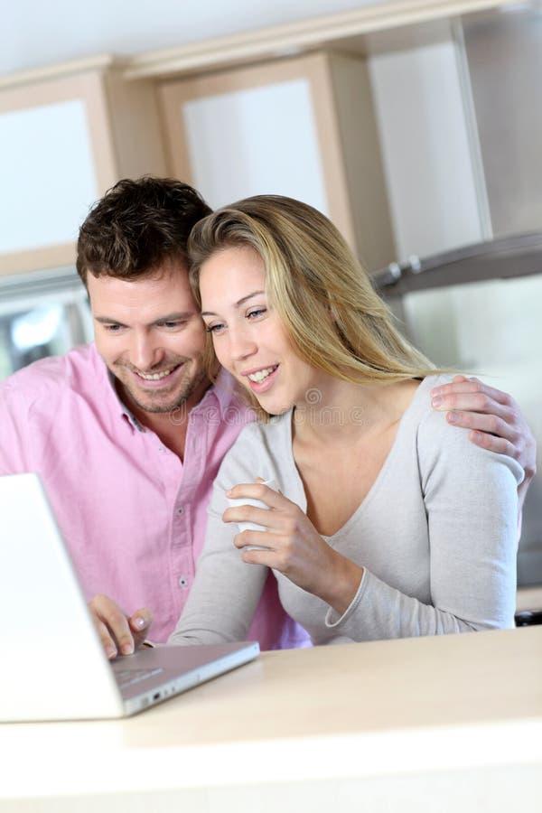 Vrolijk paar die thuis laptop met behulp van stock afbeelding