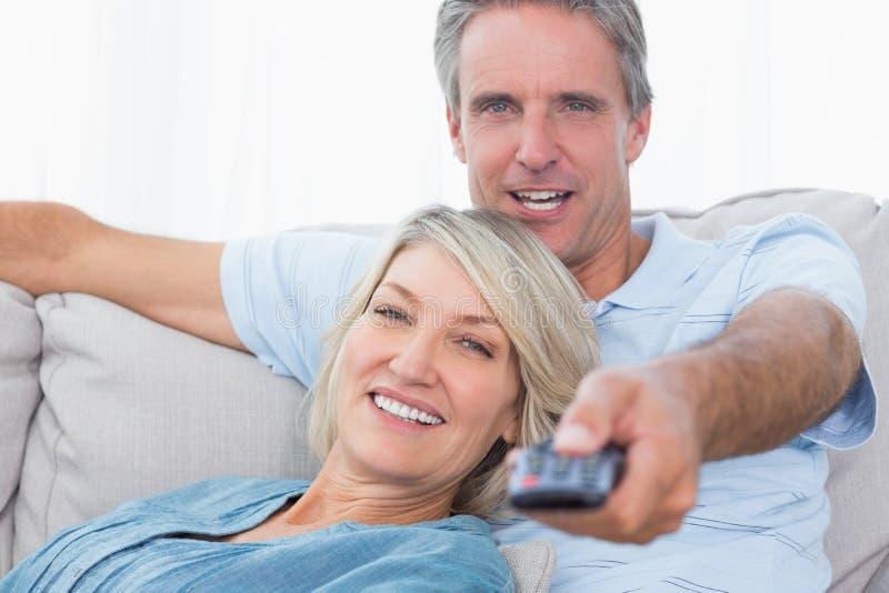 Vrolijk paar die thuis op het letten TV ontspannen royalty-vrije stock foto