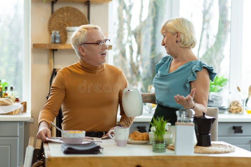 Vrolijk paar die tijdens ontbijt spreken terwijl het zitten bij de keuken stock afbeeldingen