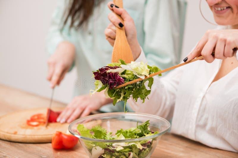 Vrolijk paar die verse salade koken samen bij keuken royalty-vrije stock foto