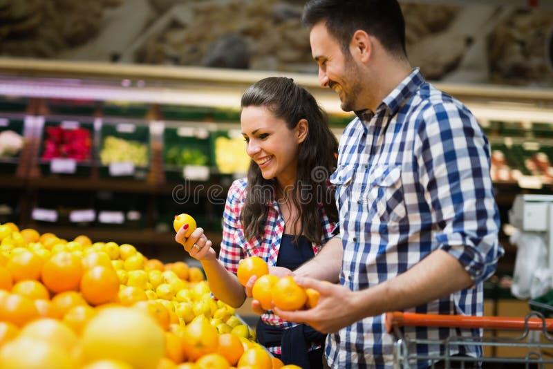 Vrolijk paar die voor organisch fruit winkelen royalty-vrije stock foto