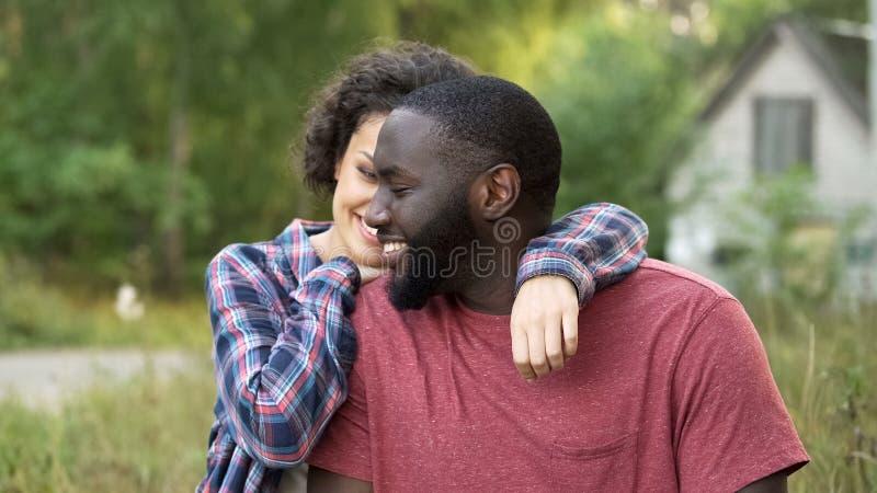 Vrolijk paar die, vrouw die brede schouders van haar echtgenoot bewonderen in openlucht koesteren stock afbeeldingen