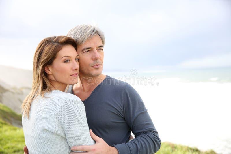 Vrolijk paar die zich door de kust bevinden stock foto's