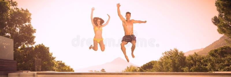 Vrolijk paar die in zwembad springen stock afbeeldingen