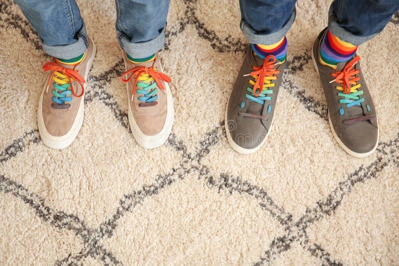 Vrolijk paar met kleurrijke sokken die zich op tapijt, hoogste mening bevinden royalty-vrije stock afbeeldingen