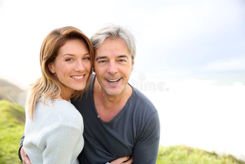 Vrolijk paar op middelbare leeftijd op kust stock foto