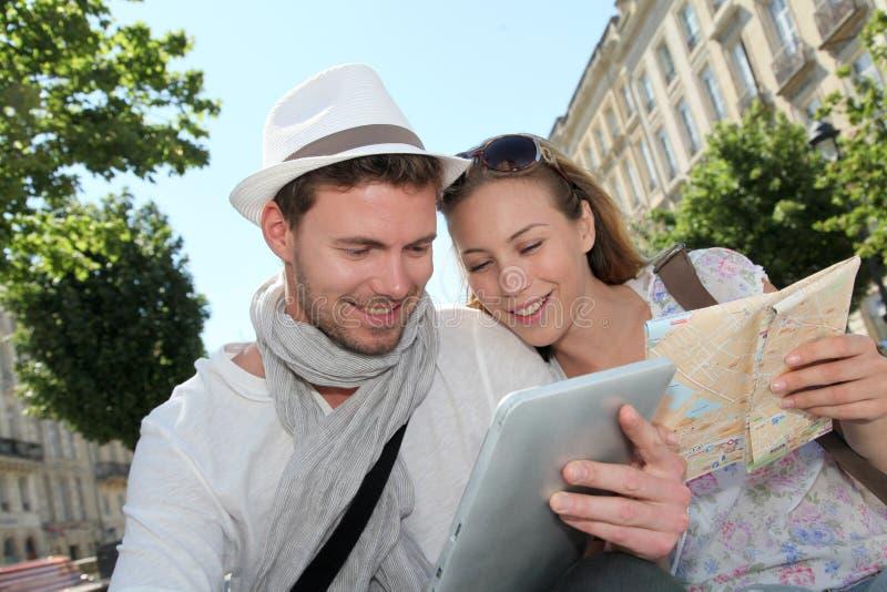 Vrolijk paar van toeristen die tablet en kaart gebruiken royalty-vrije stock fotografie