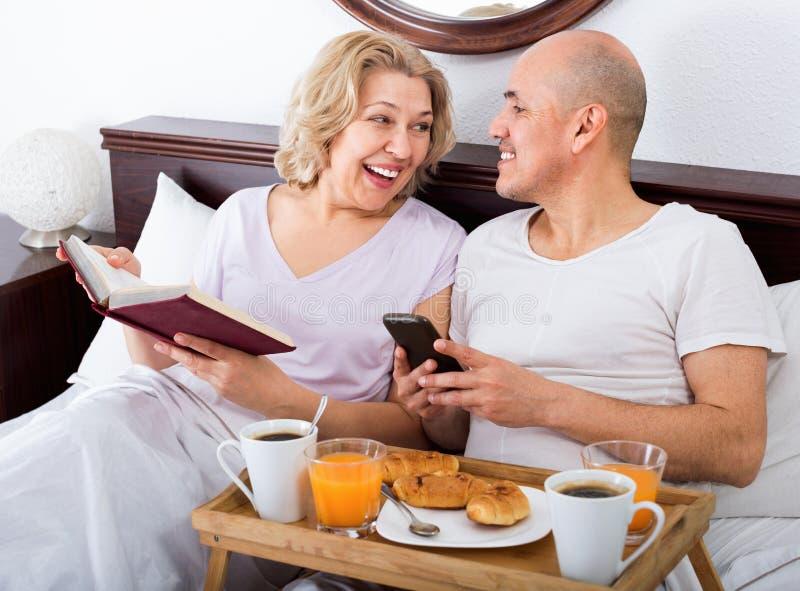 Vrolijk positief die rijpe volwassenen glimlachen die met ontbijt stellen royalty-vrije stock foto